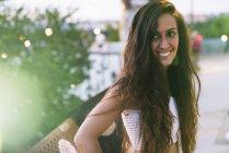 Retrato de bela jovem sorridente com cabelos castanhos longos ao ar livre — Fotografia de Stock