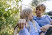 Мать и дочь отдыхают в саду — стоковое фото