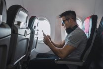 Man in airplane, using smartphone, headphones — Stock Photo