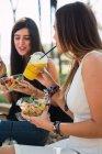 Filles assises dans un parc, mangeant de la salade,, buvant du jus — Photo de stock