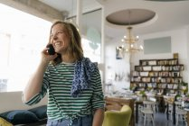 Laughing young woman on cell phone in a cafe — Stock Photo