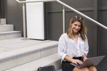 Ritratto di donna d'affari sorridente seduta sulle scale e che utilizza il computer portatile — Foto stock