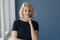 Портрет уверенной блондинки у окна — стоковое фото
