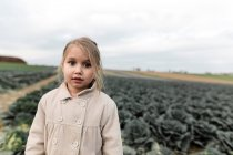 Portrait of a girl standing on a cabbage field — Stock Photo