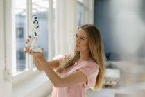 Портрет молодої жінки дивлячись на іграшковий робот — стокове фото