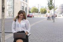 Donna d'affari sorridente che utilizza il computer portatile all'aperto — Foto stock