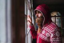 Портрет застенчивого мужчины с бородой в куртке с капюшоном, выглядывающего из окна — стоковое фото