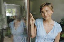 Portrait de femme souriante à la porte-fenêtre — Photo de stock