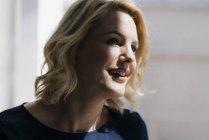 Portrait de femme blonde souriante à la lumière du soleil à la fenêtre — Photo de stock