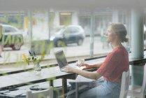 Молода жінка з чашкою кави і ноутбуком сидить у вікні в кафе — стокове фото