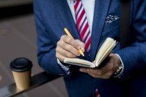 Close-up do empresário escrevendo no diário ao ar livre — Fotografia de Stock
