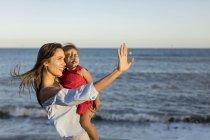Мать и дочь стоят на пляже на закате — стоковое фото