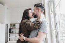 Pareja feliz abrazándose en casa - foto de stock