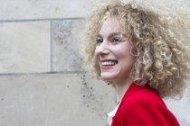 Verticale de femme blonde riante avec des boucles — Photo de stock