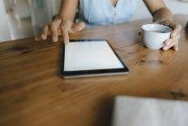 Primo piano della donna seduta a tavola a casa con tazza di caffè e tablet — Foto stock