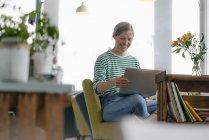 Sorrindo jovem mulher usando laptop em um café — Fotografia de Stock