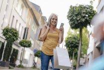 Улыбающаяся женщина на улице, несущая сумки, смотрящие на сотовый телефон — стоковое фото