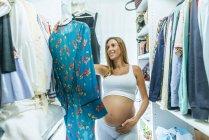 Mulher grávida olhando para roupas em um camarim — Fotografia de Stock