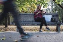 Mujer joven con bolsa de compras sentada en el banco en otoño usando mini tableta - foto de stock