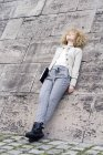 Fashionable blond woman with folder leaning against wall and having a rest — Stock Photo