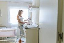 Mulher grávida preparando o quarto do bebê — Fotografia de Stock