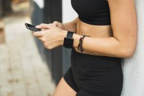 Adatta giovane donna con uno smartwatch, utilizzando lo smartphone — Foto stock
