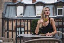 Retrato de uma jovem loira sentada no terraço e bebendo café — Fotografia de Stock