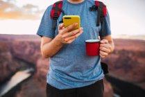 Hombre joven que se queda con la copa roja y utiliza teléfonos inteligentes - foto de stock