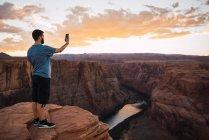 США, Аризона, река Колорадо, Лошадиная избушка, молодой человек на смотровой площадке с помощью смартфона, фотографирование — стоковое фото