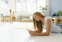 Sorrindo jovem deitada no chão em seu sótão e olhando para o telefone celular — Fotografia de Stock