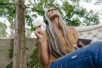 Donna con cellulare seduto in giardino ad ascoltare musica con le cuffie — Foto stock