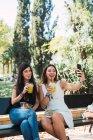 Amigas sentadas em um parque, comendo salada,, bebendo suco e tirando selfies — Fotografia de Stock