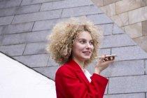 Verticale de femme blonde de sourire avec des anneaux utilisant le manteau rouge de procès parlant sur le téléphone portable — Photo de stock