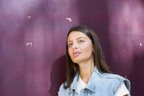 Ritratto di giovane donna che sogna ad occhi aperti davanti allo sfondo viola — Foto stock