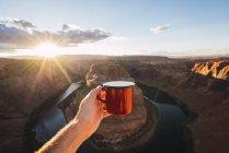 Estados Unidos, Arizona, Colorado River, Horseshoe Bend, joven sosteniendo copa roja - foto de stock