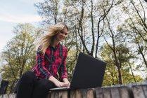 Ritratto di giovane donna sorridente seduta su un banco all'aperto e che lavora su un computer portatile — Foto stock
