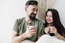 Glückliches Paar, das im Bett sitzt, Kaffee trinkt und Spaß hat — Stockfoto