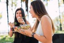 Petites amies assises dans un parc, mangeant une salade — Photo de stock