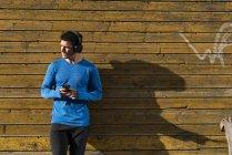Спортсмен прислонился к стене дома с сотовым телефоном и наушниками — стоковое фото