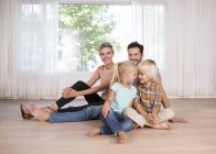 Famiglia rilassata seduta sul pavimento a casa — Foto stock