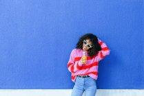 Retrato de jovem sorridente com garrafa de suco de laranja em pé na frente da parede azul — Fotografia de Stock
