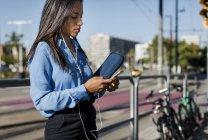 Donna d'affari utilizzando smartphone, tenendo borsa per computer portatile — Foto stock