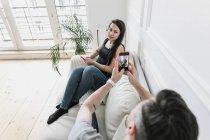 Couple assis à la maison sur un canapé, utilisant son téléphone intelligent — Photo de stock