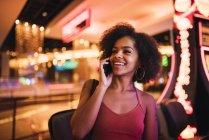 EUA, Nevada, Las Vegas, retrato de uma jovem feliz ao telefone celular em um cassino — Fotografia de Stock