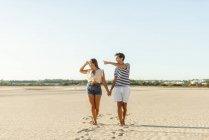 Jovem casal andando de mãos dadas na praia — Fotografia de Stock