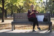 Mujer joven con bolsa de compras sentado en el banco en otoño y el uso de mini tableta - foto de stock