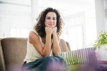 Mulher confiante sentada em seu sofá, sorrindo — Fotografia de Stock