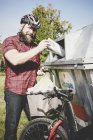 Велосипедист в шлеме, перерабатывающий бумагу в бумажном банке — стоковое фото