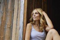 Mulher loira sorridente na frente da cabana de madeira — Fotografia de Stock