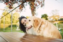 Portrait of young woman with her Golden retriever dog resting in a park — Stock Photo